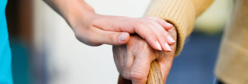 A young hand rests on top of an elderly hand.