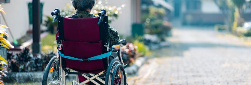 seniors with Alzheimer's disease being outdoors in a wheelchair.