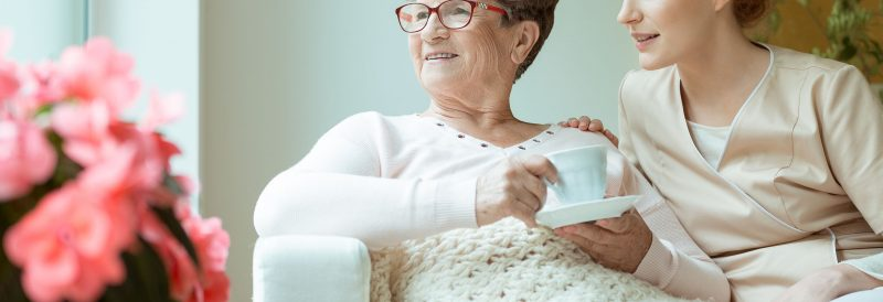 Smiling nurse providing senior home care services by sitting with elder woman on white sofa while drinking tea in living room