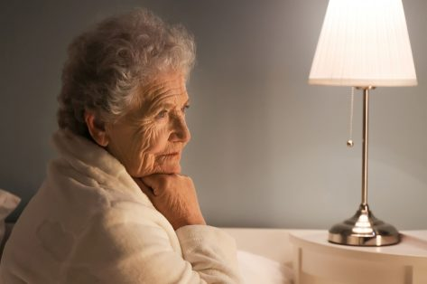 elderly woman with sundowning syndrome sitting next to night lamp